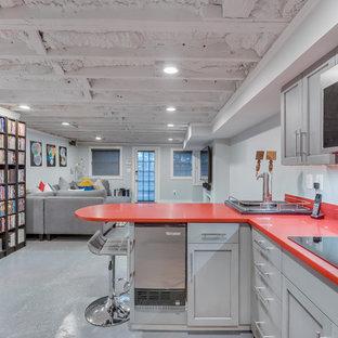 ワシントンD.C.の中くらいのコンテンポラリースタイルのおしゃれなウェット バー (コの字型、アンダーカウンターシンク、シェーカースタイル扉のキャビネット、グレーのキャビネット、クオーツストーンカウンター、コンクリートの床、グレーの床、赤いキッチンカウンター) の写真