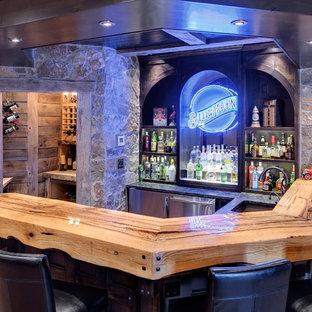ミネアポリスのラスティックスタイルのおしゃれな着席型バー (コの字型、アンダーカウンターシンク、木材カウンター、濃色木目調キャビネット、コンクリートの床、ベージュのキッチンカウンター) の写真