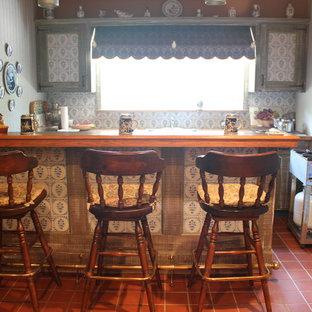 Esempio di un bancone bar stile rurale di medie dimensioni con ante in stile shaker, ante con finitura invecchiata, top in legno, paraspruzzi multicolore, paraspruzzi in gres porcellanato, pavimento con piastrelle in ceramica e pavimento rosso