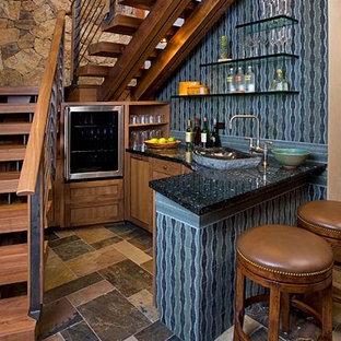ニューヨークの小さいラスティックスタイルのおしゃれな着席型バー (L型、シェーカースタイル扉のキャビネット、中間色木目調キャビネット、御影石カウンター、青いキッチンパネル、スレートの床) の写真