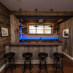 Ispirazione per un grande bancone bar stile rurale con lavello da incasso, ante in stile shaker, ante in legno chiaro, top in cemento, paraspruzzi blu, paraspruzzi con lastra di vetro, parquet scuro e pavimento marrone