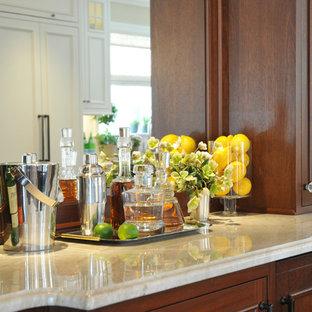 Photo of a medium sized traditional single-wall home bar in Boston with no sink, recessed-panel cabinets, dark wood cabinets, marble worktops, mirror splashback, medium hardwood flooring, brown floors and beige worktops.