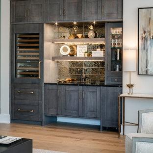 シカゴの広いコンテンポラリースタイルのおしゃれなウェット バー (シェーカースタイル扉のキャビネット、グレーのキャビネット、黒いキッチンパネル、無垢フローリング、茶色い床、黒いキッチンカウンター) の写真