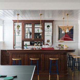 Aménagement d'un très grand bar de salon avec évier classique en L avec un sol en bois foncé, un sol marron, un évier encastré, un placard à porte vitrée, des portes de placard en bois brun, un plan de travail en bois, une crédence en carreau de miroir et un plan de travail marron.