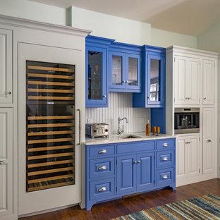 ボストンのトラディショナルスタイルのおしゃれなウェット バー (アンダーカウンターシンク、ガラス扉のキャビネット、青いキャビネット、ベージュキッチンパネル、濃色無垢フローリング、ベージュのキッチンカウンター) の写真