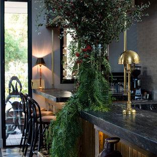Foto di un grande angolo bar con lavandino stile rurale con consolle stile comò, ante in legno scuro, top in granito, pavimento in cemento, pavimento verde e top nero