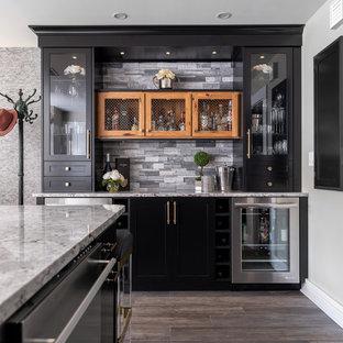 ボストンのトランジショナルスタイルのおしゃれなホームバー (I型、シンクなし、ガラス扉のキャビネット、黒いキャビネット、グレーのキッチンパネル、茶色い床、グレーのキッチンカウンター) の写真