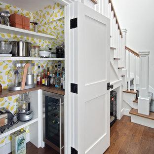 Foto di un piccolo angolo bar moderno con nessun lavello, nessun'anta, ante bianche, top in legno, pavimento in legno massello medio, pavimento marrone, top marrone e paraspruzzi multicolore