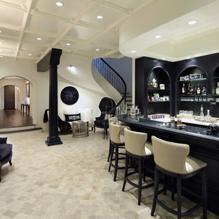 Idées déco pour un bar de salon parallèle victorien de taille moyenne avec des tabourets, un évier encastré, un placard avec porte à panneau surélevé, des portes de placard noires, un plan de travail en surface solide, un sol en carrelage de céramique et un sol beige.