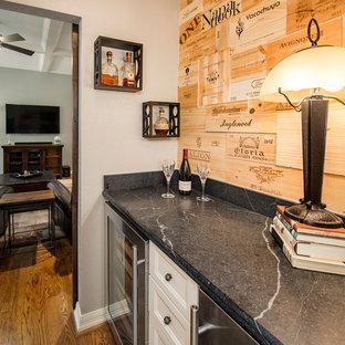 ダラスの小さいトラディショナルスタイルのおしゃれなホームバー (I型、シェーカースタイル扉のキャビネット、白いキャビネット、ソープストーンカウンター、茶色いキッチンパネル、無垢フローリング) の写真