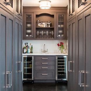 ニューヨークの広いトランジショナルスタイルのおしゃれなウェット バー (I型、茶色いキャビネット、白いキッチンパネル、白いキッチンカウンター) の写真