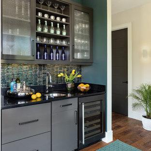 Immagine di un armadio bar tradizionale con lavello sottopiano, ante lisce, ante grigie, paraspruzzi verde, parquet scuro e top nero