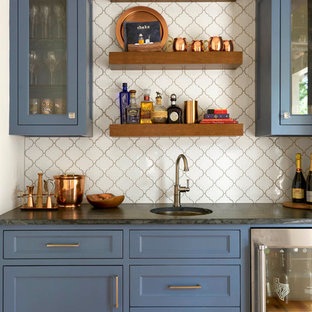 Design ideas for a rural single-wall wet bar in Dallas with a submerged sink, blue cabinets, white splashback and glass-front cabinets.