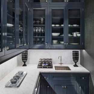 ニューヨークの中くらいのトランジショナルスタイルのおしゃれなウェット バー (L型、アンダーカウンターシンク、ガラス扉のキャビネット、青いキャビネット、大理石カウンター、白いキッチンパネル、大理石のキッチンパネル、濃色無垢フローリング、茶色い床) の写真