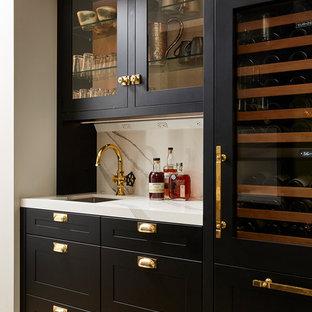ミネアポリスのトランジショナルスタイルのおしゃれなウェット バー (アンダーカウンターシンク、シェーカースタイル扉のキャビネット、黒いキャビネット、クオーツストーンカウンター、白いキッチンパネル、石スラブのキッチンパネル、淡色無垢フローリング、白いキッチンカウンター、I型) の写真