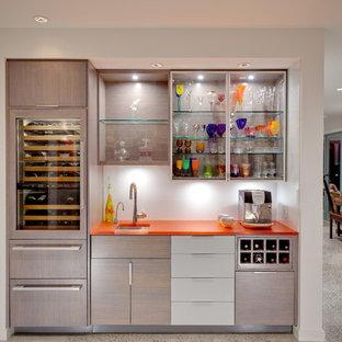 バンクーバーのコンテンポラリースタイルのおしゃれなウェット バー (I型、アンダーカウンターシンク、フラットパネル扉のキャビネット、淡色木目調キャビネット、白いキッチンパネル、オレンジのキッチンカウンター) の写真