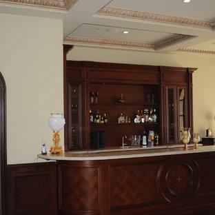 Esempio di un bancone bar di medie dimensioni con lavello sottopiano, ante con riquadro incassato, ante in legno bruno, top in pietra calcarea, pavimento in pietra calcarea e pavimento beige