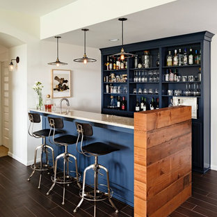 Large transitional galley dark wood floor and brown floor seated home bar photo in Portland with open cabinets, blue cabinets and granite countertops