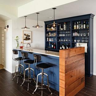 Foto på en stor vintage parallell hemmabar med stolar, med öppna hyllor, blå skåp, granitbänkskiva, mörkt trägolv och brunt golv