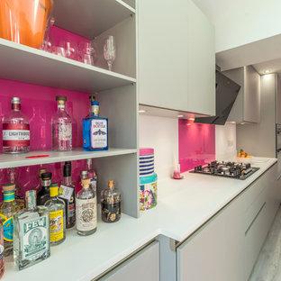 マンチェスターの広いコンテンポラリースタイルのおしゃれなホームバー (フラットパネル扉のキャビネット、グレーのキャビネット、御影石カウンター、ピンクのキッチンパネル、ガラス板のキッチンパネル、クッションフロア) の写真