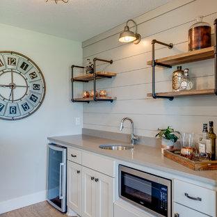 Cette photo montre un bar de salon avec évier linéaire nature avec un évier encastré, un placard à porte shaker, des portes de placard blanches, une crédence blanche, une crédence en bois, un plan de travail gris et un sol en bois brun.