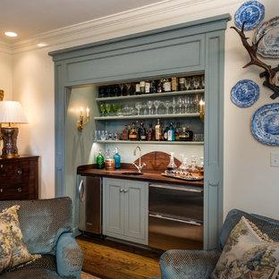 Immagine di un armadio bar tradizionale di medie dimensioni con pavimento marrone, lavello sottopiano, ante con riquadro incassato, ante blu, top in legno, parquet scuro e top marrone