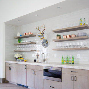 Example of a large mountain style single-wall light wood floor and beige floor wet bar design with a drop-in sink, flat-panel cabinets, medium tone wood cabinets, quartzite countertops, white backsplash, porcelain backsplash and beige countertops