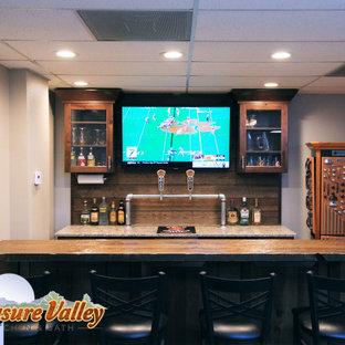 Idee per un piccolo bancone bar stile rurale con ante con bugna sagomata, ante in legno bruno, top in quarzo composito, paraspruzzi marrone e paraspruzzi in perlinato