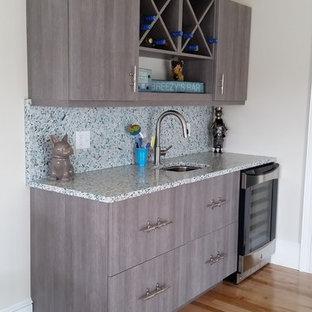 Idee per un angolo bar con lavandino stile marinaro di medie dimensioni con lavello sottopiano, ante lisce, ante grigie, top in vetro riciclato, paraspruzzi blu e parquet chiaro