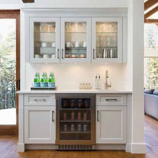 Foto de bar en casa lineal, tradicional renovado, grande, con armarios estilo shaker, puertas de armario grises, encimera de cuarzo compacto, salpicadero blanco, salpicadero de azulejos tipo metro y suelo de madera en tonos medios
