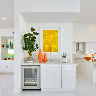 Inspiration for a small midcentury single-wall wet bar in Orange County with flat-panel cabinets, white cabinets, marble worktops, grey worktops, a submerged sink and white floors.