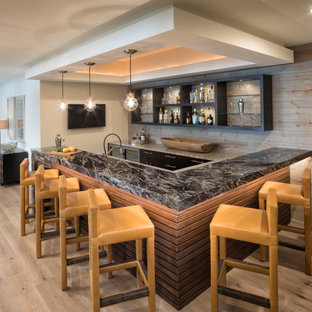 Seated home bar - large contemporary u-shaped light wood floor and brown floor seated home bar idea in Minneapolis with black cabinets, granite countertops, brown backsplash, wood backsplash and black countertops