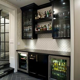 Aménagement d'un bar de salon linéaire classique avec un placard à porte vitrée, des portes de placard noires, une crédence blanche, aucun évier ou lavabo, un sol noir et un plan de travail noir.
