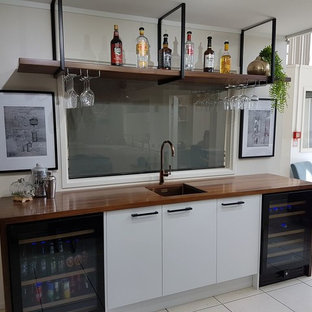Example of a huge minimalist single-wall wet bar design in Other with an undermount sink, white cabinets and wood countertops