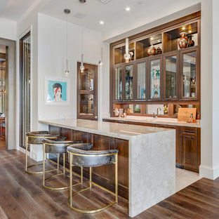 Inspiration for an expansive traditional single-wall wet bar in Miami with medium wood cabinets, marble worktops, medium hardwood flooring, brown floors, a submerged sink, recessed-panel cabinets, mirror splashback and beige worktops.
