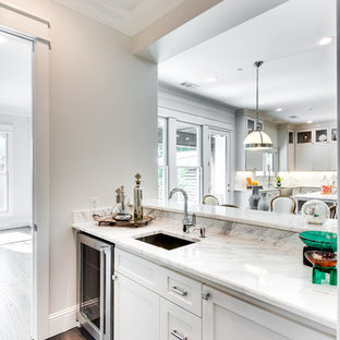 Photo of a traditional wet bar in Dallas with a submerged sink, shaker cabinets, white cabinets, marble worktops, white splashback, dark hardwood flooring, brown floors and white worktops.