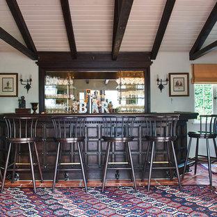 Immagine di un grande bancone bar mediterraneo con ante in legno bruno, paraspruzzi a specchio, pavimento in terracotta e pavimento arancione