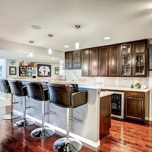 デンバーの広いモダンスタイルのおしゃれな着席型バー (I型、アンダーカウンターシンク、シェーカースタイル扉のキャビネット、茶色いキャビネット、御影石カウンター、濃色無垢フローリング、茶色い床、グレーのキッチンパネル、メタルタイルのキッチンパネル、白いキッチンカウンター) の写真