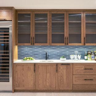 Esempio di un angolo bar con lavandino costiero con lavello sottopiano, ante di vetro, ante in legno scuro, paraspruzzi blu, parquet chiaro, pavimento beige e top bianco