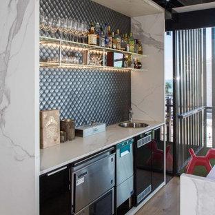 Idee per un grande bancone bar minimalista con ante lisce, lavello da incasso, ante nere, top piastrellato, paraspruzzi grigio, paraspruzzi con piastrelle a mosaico, pavimento in legno massello medio, pavimento marrone e top bianco