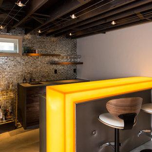 Foto di un bancone bar minimal di medie dimensioni con paraspruzzi grigio, pavimento in cemento, lavello sottopiano, ante lisce, ante in legno bruno, top in vetro, paraspruzzi con piastrelle a mosaico e top giallo
