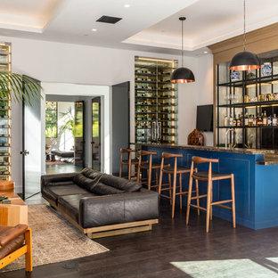 ロサンゼルスの巨大なコンテンポラリースタイルのおしゃれな着席型バー (オープンシェルフ、ミラータイルのキッチンパネル、濃色無垢フローリング、茶色い床、コの字型、ベージュのキャビネット、御影石カウンター) の写真