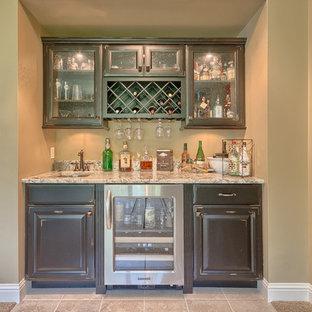 Esempio di un piccolo angolo bar con lavandino classico con lavello sottopiano, ante in legno bruno, top in granito, pavimento con piastrelle in ceramica, ante con bugna sagomata e pavimento beige