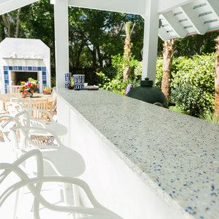 チャールストンの広いビーチスタイルのおしゃれな着席型バー (I型、シェーカースタイル扉のキャビネット、白いキャビネット、再生ガラスカウンター、コンクリートの床、グレーの床、ドロップインシンク) の写真