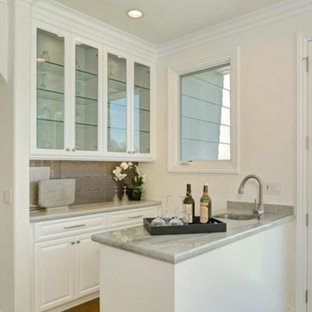 Photo of a small modern galley wet bar in Los Angeles with a submerged sink, raised-panel cabinets, white cabinets, marble worktops, beige splashback, porcelain splashback and light hardwood flooring.