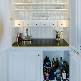 Photo of a small traditional wet bar in DC Metro with a submerged sink, raised-panel cabinets, white cabinets, granite worktops and medium hardwood flooring.
