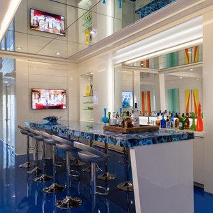 ニューヨークのコンテンポラリースタイルのおしゃれな着席型バー (ミラータイルのキッチンパネル、青い床、青いキッチンカウンター) の写真