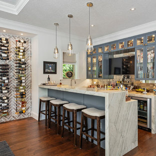 Photo of a beach style breakfast bar in Orlando with glass-front cabinets, grey cabinets, marble worktops, metal splashback, dark hardwood flooring and white worktops.