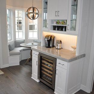 Exempel på en liten klassisk linjär hemmabar, med vita skåp, bänkskiva i kvartsit, mörkt trägolv och skåp i shakerstil