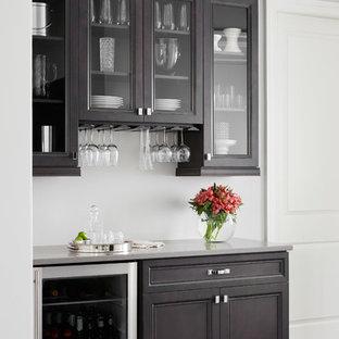 Cette photo montre un petit bar de salon chic avec des portes de placard en bois sombre, un plan de travail en quartz modifié, un sol en bois foncé, aucun évier ou lavabo et un placard à porte vitrée.